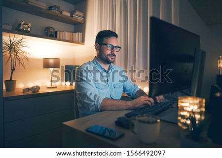 Modern young man working remotely from home at night.  #1566492097