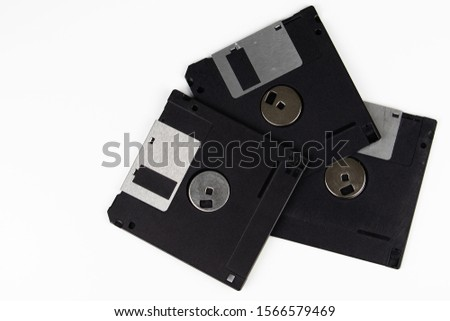 Three old floppy disks are lying on top of each other on a table with a white background. The color of the floppy disks is black. #1566579469