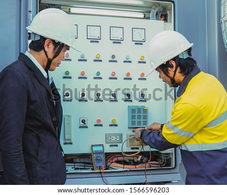 Businessmen and engineers are talking about problems and electricity production in large power plants, dem uses a multimeter to check for problems. #1566596203