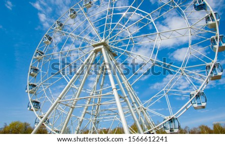 Ferris wheel an amusement-park or fairground ride consisting of a giant vertical revolving wheel with passenger cars suspended on its outer edge. #1566612241