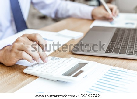 Calculate the calculator, Male employees work in private rooms Calculating company revenue figures with calculator, Financial accounting concepts #1566627421