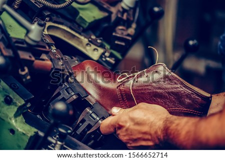 Experienced shoemaker using a special machine for putting shoes on the mold, in the handmade footwear industry. Selective focus and small depth of field. Royalty-Free Stock Photo #1566652714