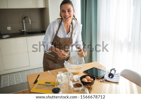 Young woman in the kitchen and inserts ingredients #1566678712