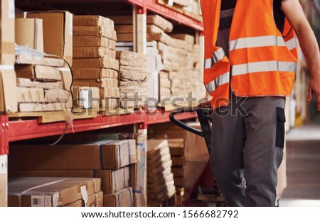Young male worker in uniform is in the warehouse pushing pallet truck. #1566682792