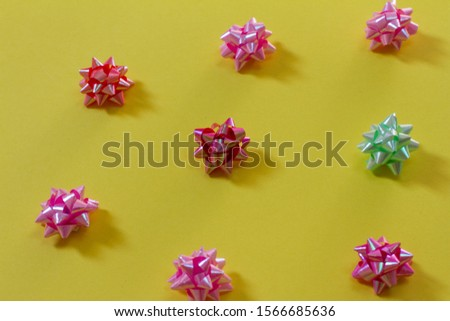 many bows on a yellow background. bows on a colored background. for postcards. Christmas tree decoration. space for text. the view from the top. 2020. gift #1566685636