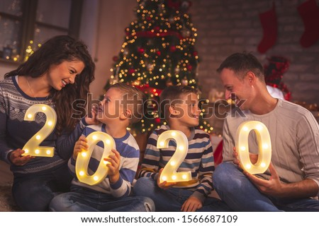 Parents celebrating New Years Eve at home with kids, sitting by the Christmas tree, holding illuminative numbers 2020 representing the upcoming New Year #1566687109
