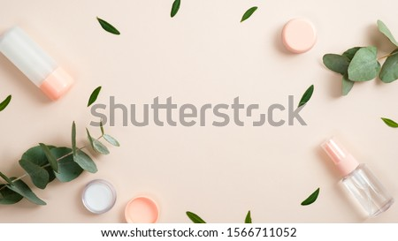 Frame made of natural organic cosmetic bottle containers with green herbal leaves on pastel beige background. Natural beauty product concept. Banner mockup for beauty blog. Flat lay, top view. #1566711052
