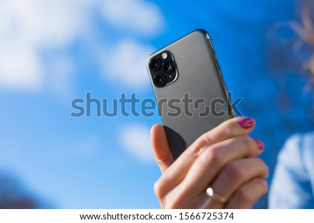 Person holding modern smartphone with triple-lens camera