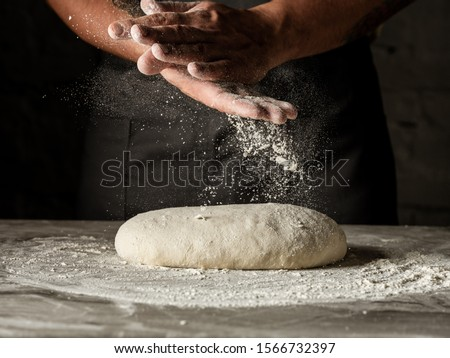 Cooking dough by chef hands for homemade pastry bread, pizza, pasta recipe preparation on table background.  #1566732397