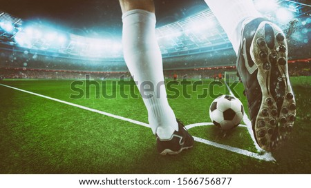 Football scene at night match with close up of a soccer shoe hitting the ball from corner kick Royalty-Free Stock Photo #1566756877
