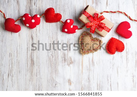 Flat lay cute composition with handmade fabric red hearts. Gift box with ribbon bow on wooden table. Happy birthday or anniversary congratulation. Romantic message template with copy space. #1566841855