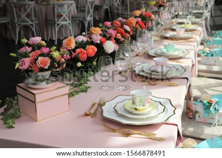 Table set up for bridal shower on bright spring day with flowers and vintage tea cups on each plate Royalty-Free Stock Photo #1566878491