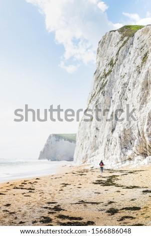 A person walks alone alone the beach next to white chalk cliffs #1566886048