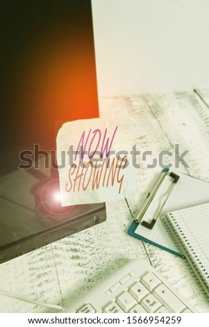 Conceptual hand writing showing Now Showing. Business photo text opportunity for the public to see something currently available Note paper taped to black screen near keyboard stationary. #1566954259