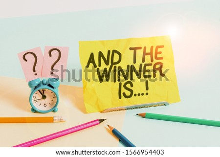 Text sign showing And The Winner Is. Conceptual photo announcing who got first place at competition or exam Mini size alarm clock beside stationary placed tilted on pastel backdrop. #1566954403