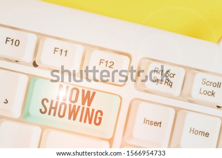 Conceptual hand writing showing Now Showing. Business photo text opportunity for the public to see something currently available White pc keyboard with note paper above the white background. #1566954733