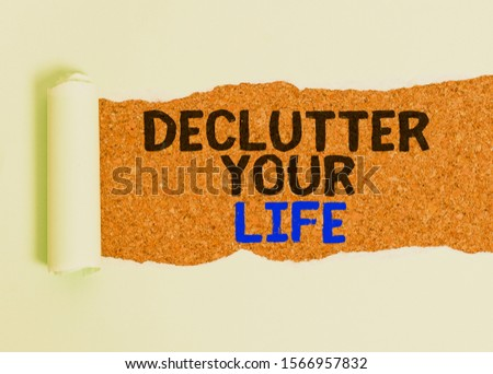 Writing note showing Declutter Your Life. Business photo showcasing To eliminate extraneous things or information in life Cardboard which is torn placed above a wooden classic table. #1566957832