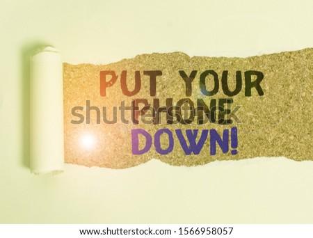Writing note showing Put Your Phone Down. Business photo showcasing end telephone connection saying goodbye caller Cardboard which is torn placed above a wooden classic table. #1566958057