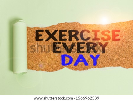 Writing note showing Exercise Every Day. Business photo showcasing move body energetically in order to get fit and healthy Cardboard which is torn placed above a wooden classic table. #1566962539