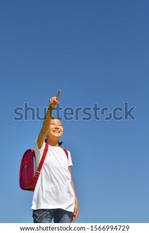 Japanese elementary school girl pointing in the blue sky #1566994729
