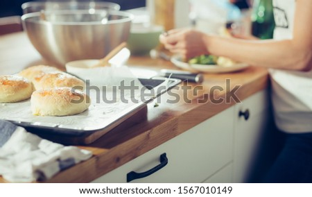 Daughter prepares a meal in the home kitchen. Kitchen mess while cooking. Preparation of burger rolls. Horizontal photography and shallow depth of field. #1567010149
