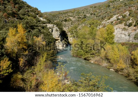 A river flows between mountains in South France, it turns right, it turns left. Trees with autumnal colours. #1567016962