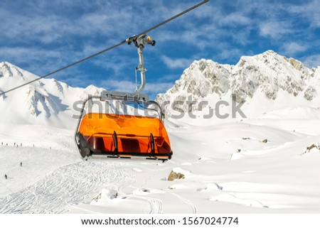 Ski lift ropeway on hilghland alpine mountain winter resort on bright sunny day. Ski chairlift cable way with people enjoy skiing and snowboarding.Banner panoramic wide view of downhill slopes #1567024774