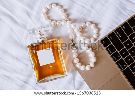 perfume bottle next to pearls and keyboard of laptop on a white sheet, Chanel stile, top view, flat lay