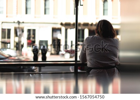 Woman sitting at table looking solemnly out to the street #1567054750
