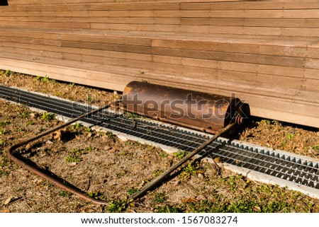 Hand pushed surface roller in front of wooden stadium benches at edge of dirt field. #1567083274