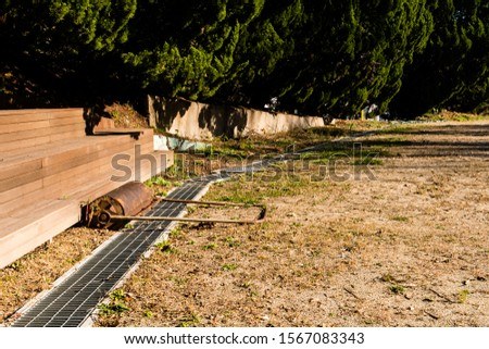 Hand pushed surface roller in front of wooden stadium benches at edge of dirt field. #1567083343