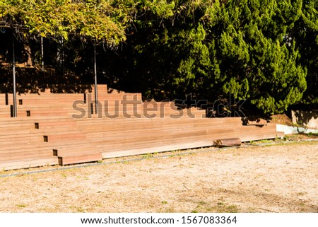 Hand pushed surface roller in front of wooden stadium benches at edge of dirt field. #1567083364