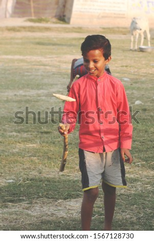 An asian happy poor tribal kid wearing colorful clothes and he is playing a famous outdoor game of india knows as Gilli danda in Hindi language. Copy space. Vertical. Old retro vintage . dANG GULI