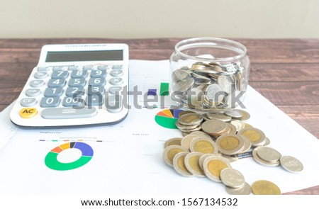Line graphs, pie graphs, and graphs of various colors printed on white paper Placed on a wooden patterned work desk Complete with a calculator and a pile of Thai baht coins #1567134532