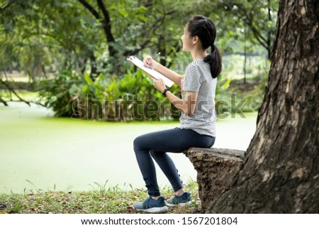 Asian child girl hobby is drawing pictures with white blank sheet of paper in clipboard, sitting in nature, beautiful female teenage  enjoys writing something about a novel or planning a vacation trip