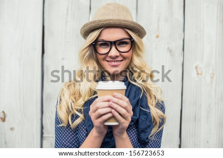 Cheerful fashionable blonde holding coffee outdoors on wooden background #156723653