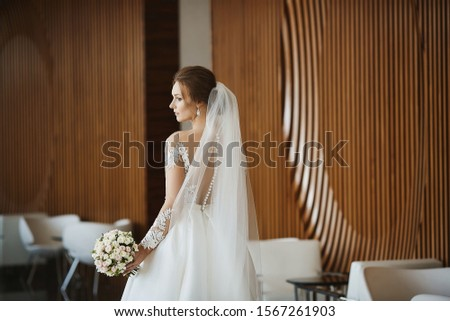 Gorgeous beauty portrait of a young bride. Beautiful bride with wedding hairstyle and makeup in a trendy dress with the bridal bouquet. Bridal fashion model with perfect body posing in the interior. #1567261903