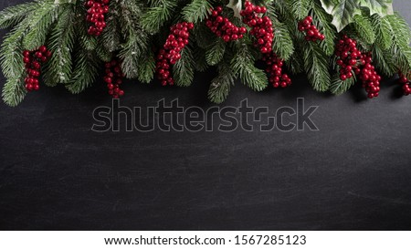 Christmas background concept. Top view of Christmas gift box red balls with spruce branches, pine cones, red berries and bell on black wooden background. #1567285123