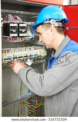 electrician at work checking wire with drawing inspecting high voltage power electric line distribution fuseboard #156731504