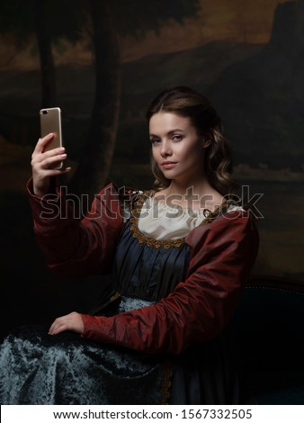 Old and new, concept. Beautiful young Renaissance style woman taking selfie on phone. Beautiful mysterious girl in the style of a Renaissance painting. #1567332505