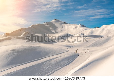 Scenic valley of hilghland alpine mountain winter resort on bright sunny day. Wintersport scene with people enjoy skiing and snowboarding on groomed pisets. panoramic wide view of downhill slopes #1567349773