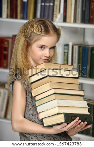 Girl with a pile of books in hands. #1567423783