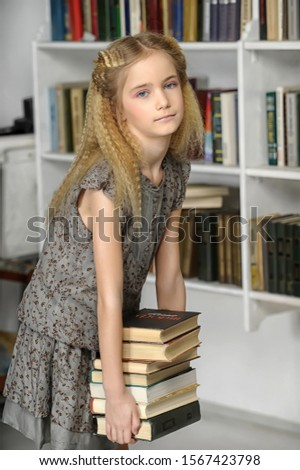 Girl with a pile of books in hands. #1567423798