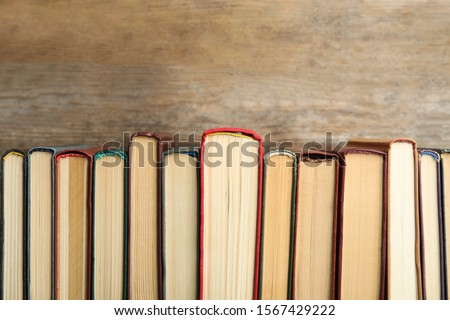 Collection of old books on wooden background Royalty-Free Stock Photo #1567429222