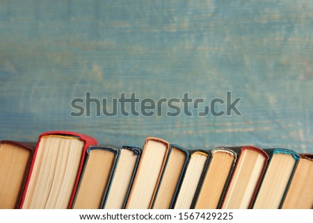 Collection of old books on blue wooden background. Space for text #1567429225
