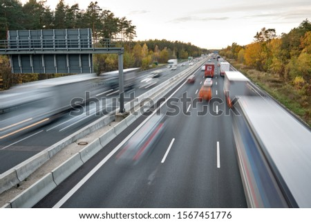 Nuremberg, Germany - November 05, 2019: Cars and trucks driving fast with lights on on an afternoon in autumn on the highway A3 near Nuremberg. #1567451776