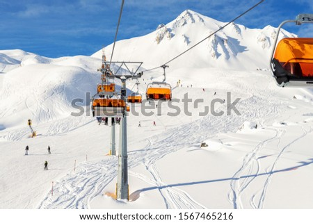 Ski lift ropeway on hilghland alpine mountain winter resort on bright sunny day. Ski chairlift cable way with people enjoy skiing and snowboarding.Banner panoramic wide view of downhill slopes #1567465216