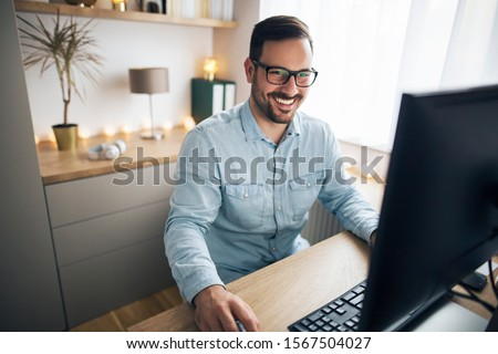 Smiling handsome freelancer working remotely from home. #1567504027