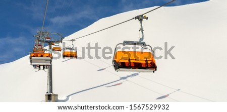 Ski lift ropeway on hilghland alpine mountain winter resort on bright sunny day. Ski chairlift cable way with people enjoy skiing and snowboarding.Banner panoramic wide view of downhill slopes #1567529932