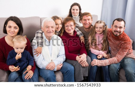 Glad large family making numerous photos during family dinner. Focus on elderly man